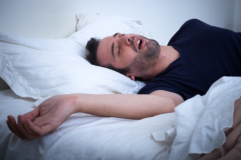 Man snoring in his bed needs help from Star Image Dentistry in Wichita Falls, Texas