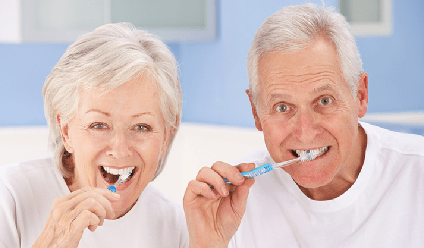 An elderly couple brsuhing thieir teeth together