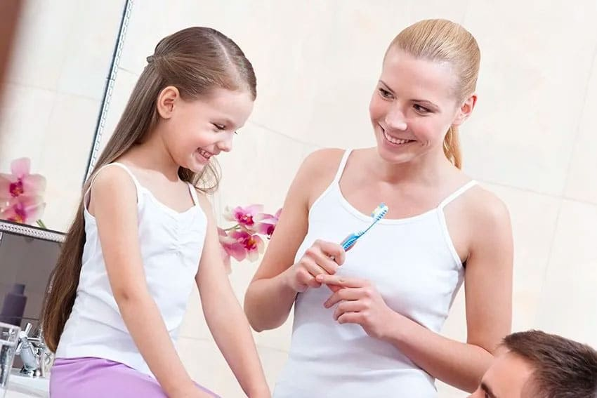 young family discussing how to best brush your teeth