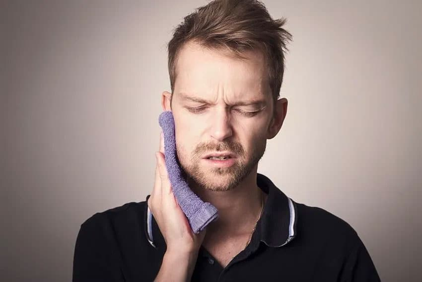 man holds a cold washcloth to his jaw due to pain