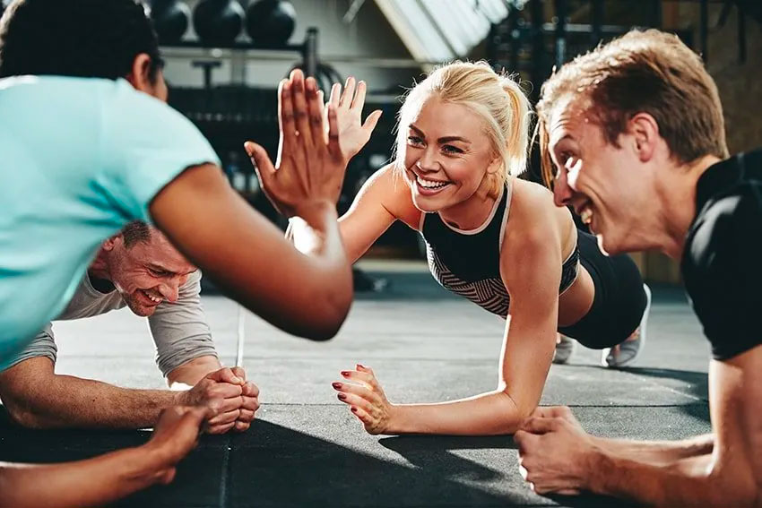 4 exercise buddies work out at the gym