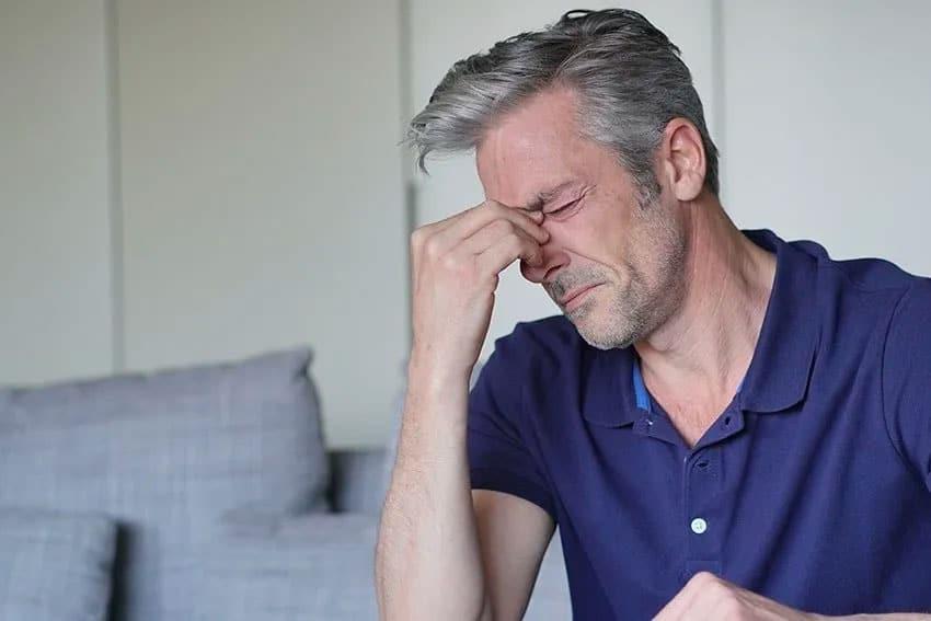 handsome mature man with a sinus headache
