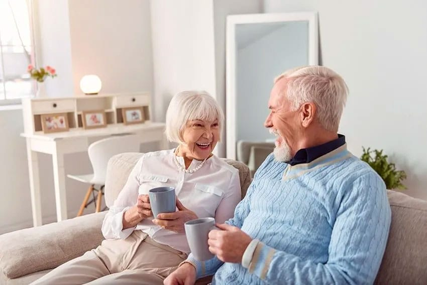 older couple enjoying a cup of coffee together on their couch