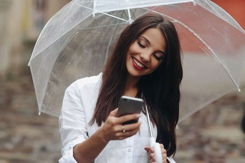 pretty young woman looking at her phone while walking with an umbrella