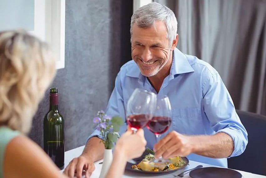 mature couple enjoying a meal with wine together