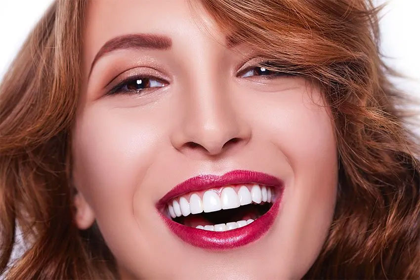 closeup of young woman with bright red lips and white teeth