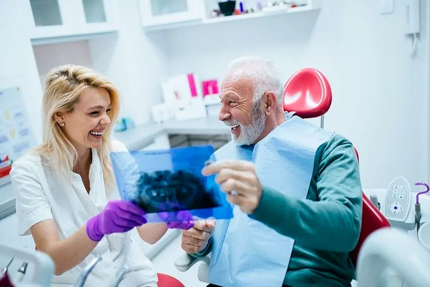 pretty female dentist shows her handsome older man his xrays while they smile together
