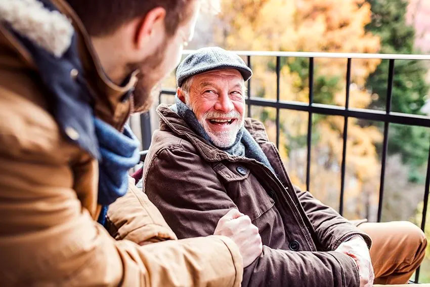 older man laughs at a joke his grandson just told him while they enjoy a cold morning in the mountains