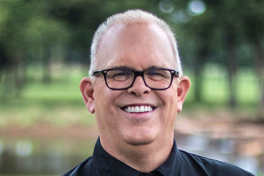 man smiles confidentially while enjoying the outdoors
