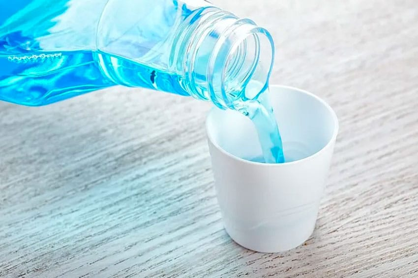 pouring a capful of blue mouthwash