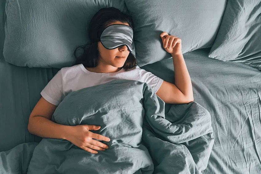 pretty young woman with sleep mask on rests peacefully in bed