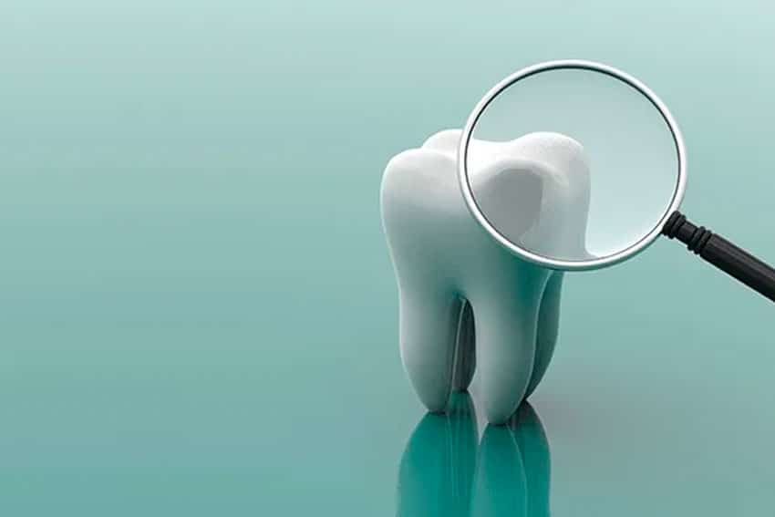 animated tooth being inspected by a magnifying glass