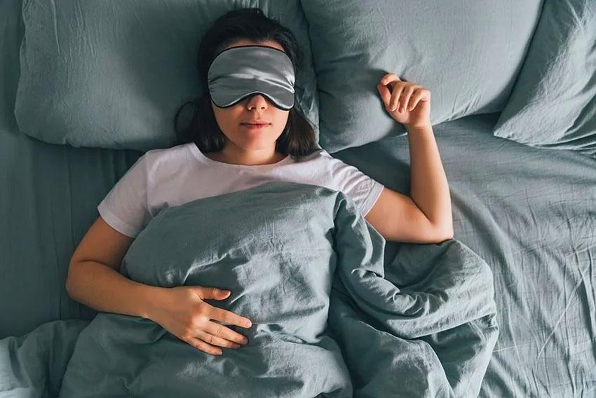 woman wearing a eye mask sleeps peacefully in bed