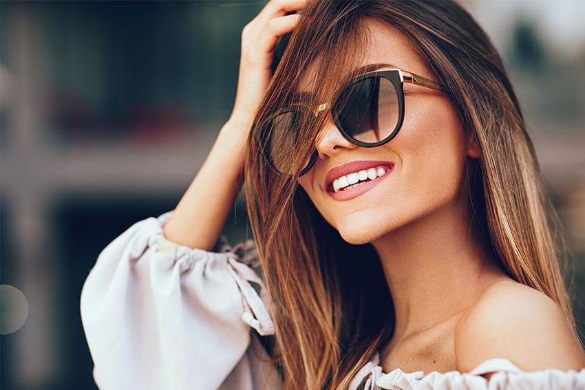beautiful young woman in large sunglasses shows off her dream smile