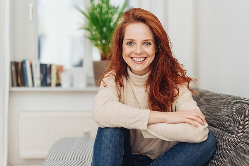 happy redhead relaxing on her couch at home